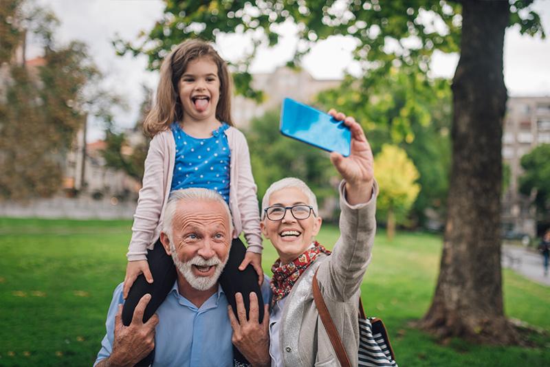 grandma and granddad taking selfie with granddaughter on shoulders