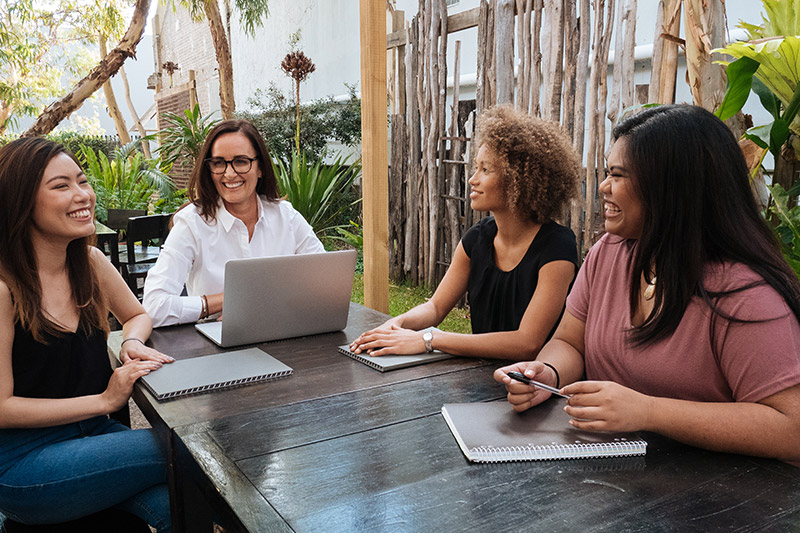 4 young female colleagues having an outdoor meeting