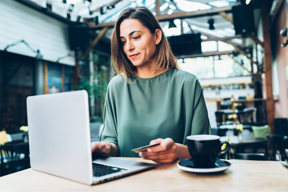 Lady with credit card enjoying coffee while online