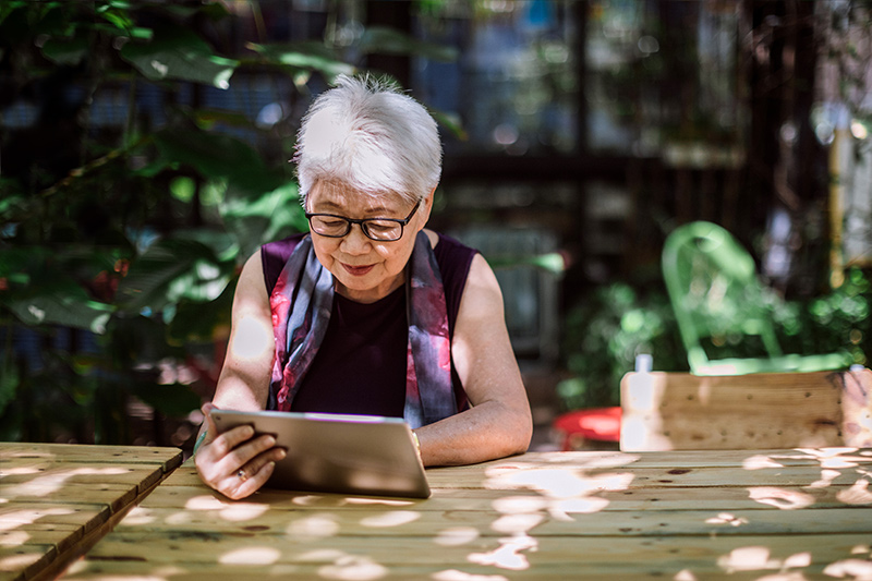 lady calmly reading a tablet outdoors