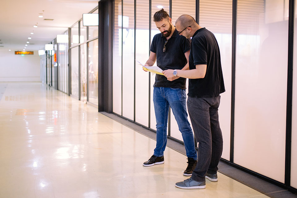 Two men reading a document in the workplace