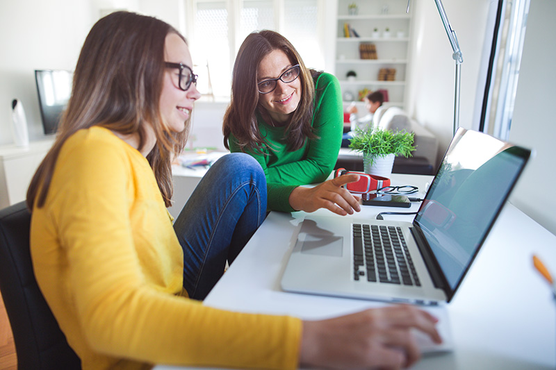teenage girl and her mum at laptop at home